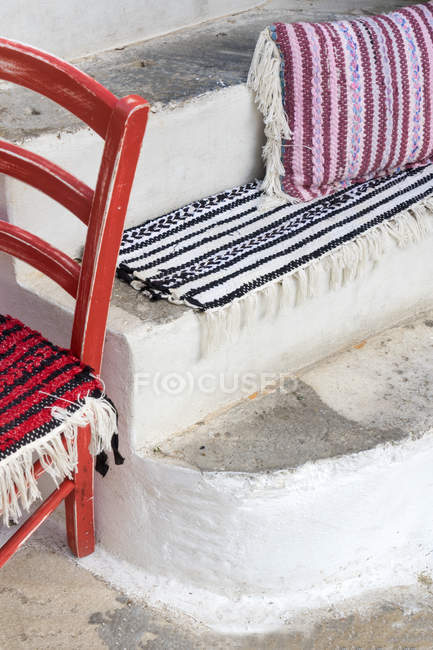 Empty red wooden chair by the stairs decorated with handmade rugs — Stock Photo