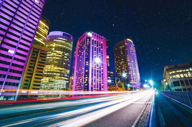 Ярко освещенные Метрополис архитектуры и дороги с движением в размытие движения — стоковое фото