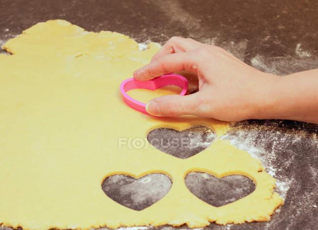 Die Hand schneiden Cookies aus Teig — Stockfoto