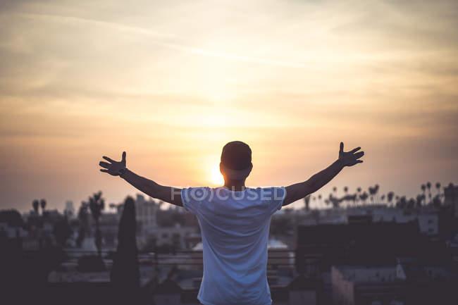 Заднього виду людини, що стоїть на даху і дивлячись на місто на заході сонця — стокове фото