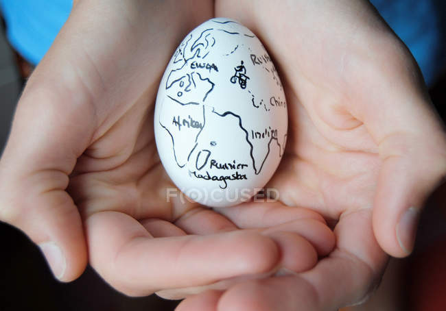 Hands holding egg with painted continents — Stock Photo