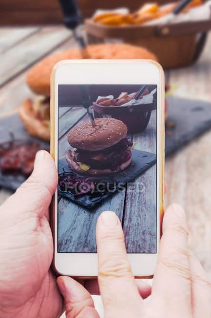 Mains, prendre des photos de burger — Photo de stock