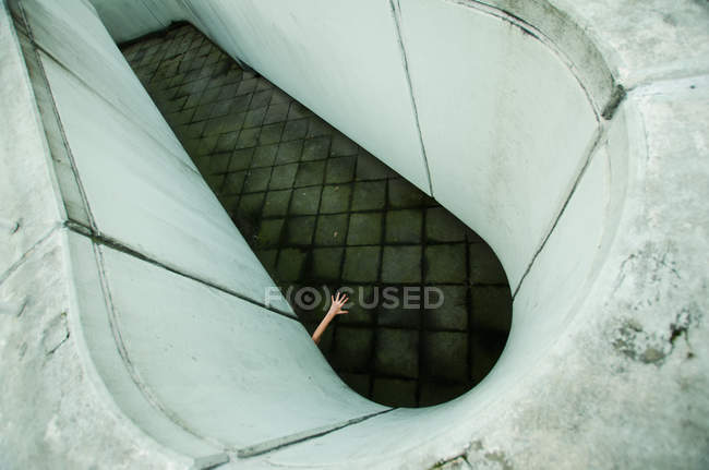 Surrealistic architectural construction and person hand downward view — Stock Photo