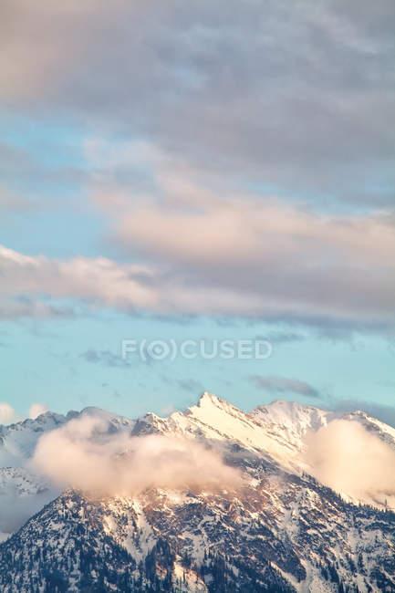Mountain peaks over sky in evening sunlight — Stock Photo