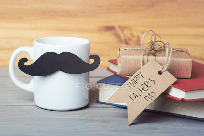 View of books and cup as present for father day at table — Stock Photo
