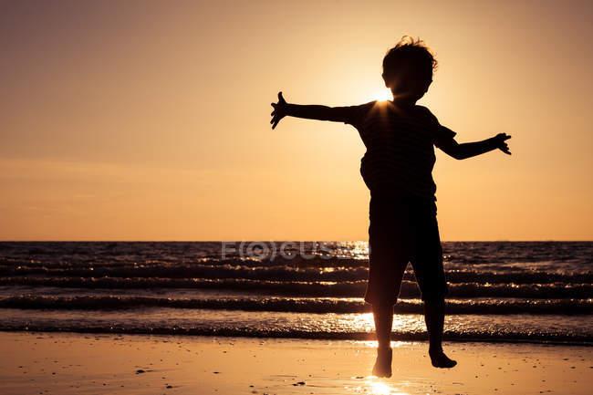 Happy little boy running on the beach — Stock Photo