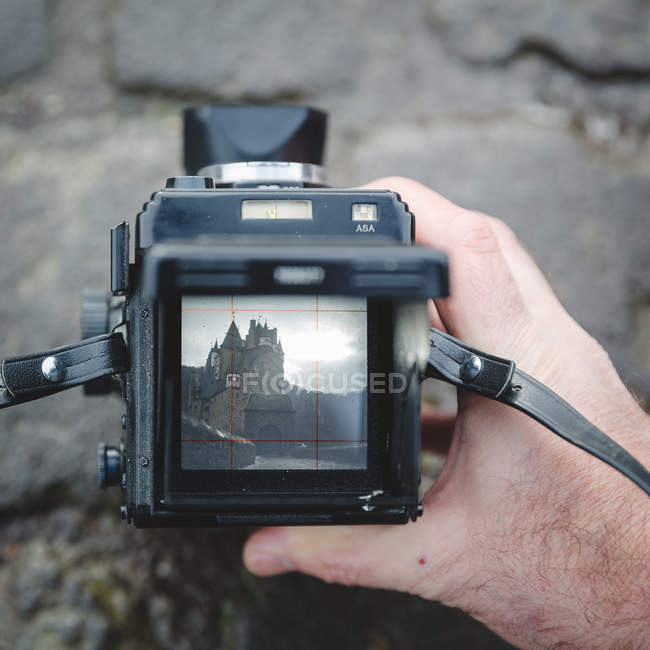 Male hand holding photo camera with castle image on screen — Stock Photo