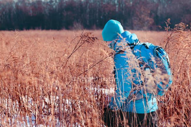 Boy hiking through meadows — Stock Photo
