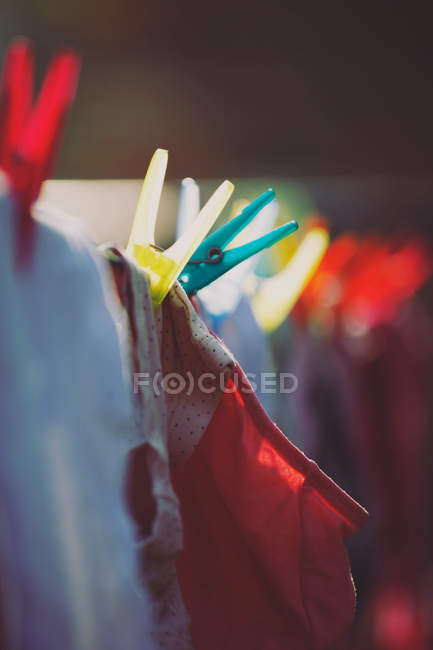 Clothesline with drying clothing and clothes pegs in bright sunlight — Stock Photo