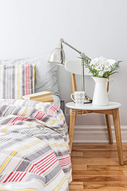 Comfortable light bedroom interior with colorful linen on bed, fresh flowers, lamp and tea cup on table — Stock Photo