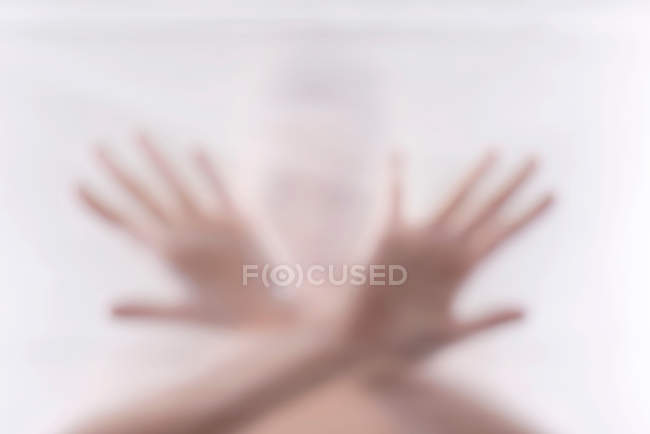 Silhouette of woman with ams crossed behind wrapping film — Stock Photo