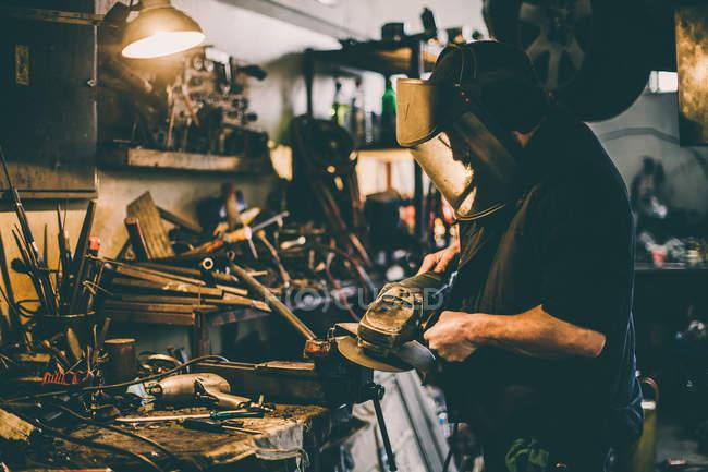 Metal grinding on steel spare part in workshop. — Stock Photo