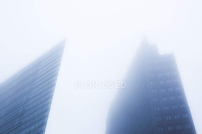 High rise building facades of modern architecture, rooftops in fog, bottom view — Stock Photo