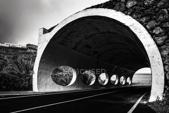 Road through tunnel with round holes — Stock Photo