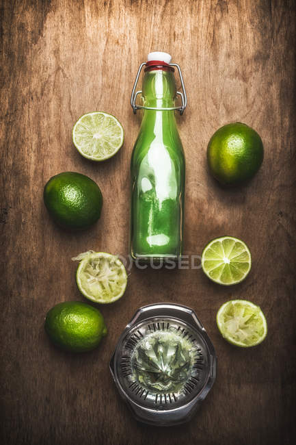 Lime halves with bottle of green cocktail — Stock Photo