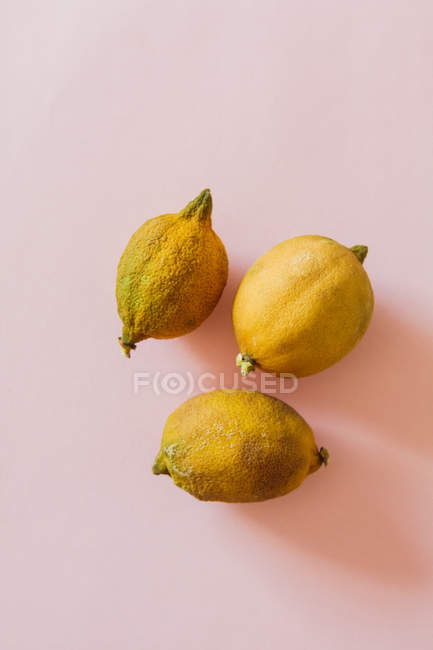 Three lemons on pink surface — Stock Photo