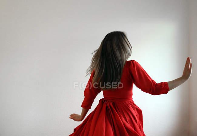 Vue arrière de la femme dans une robe rouge magnifique en salle blanche — Photo de stock