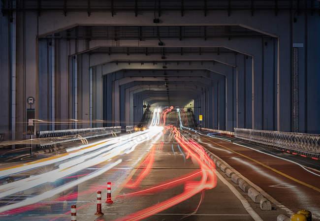 Scena urbana con traffico in movimento mosso sotto ponte — Foto stock