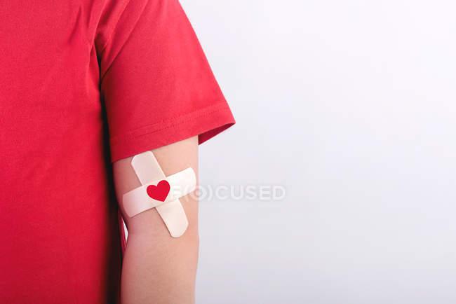 Cropped image de personne avec patch transdermique et signe de coeur rouge — Photo de stock