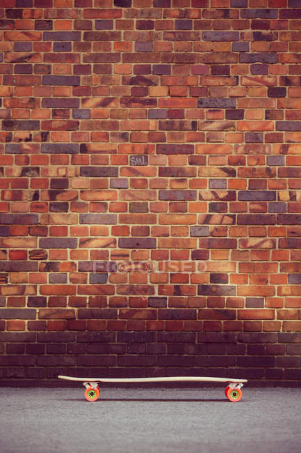 View of rough brick wall with skateboard — Stock Photo