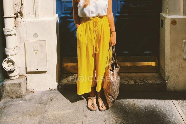 Partial view of fashionable woman standing at the street in sunlight in yellow pants and sandals holding bag — Stock Photo