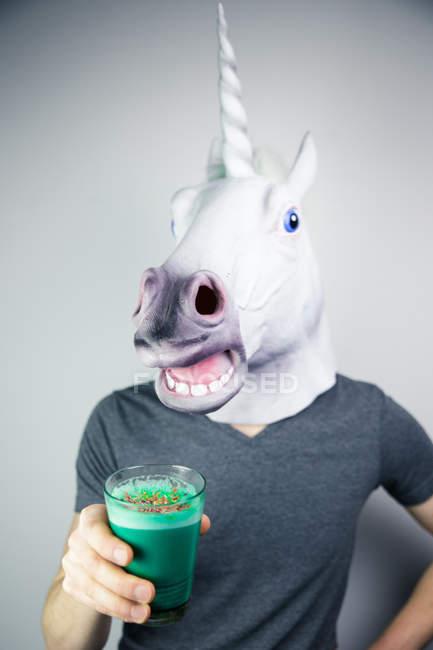 Portrait of man wearing unicorn mask holding colorful beverage - foto de stock