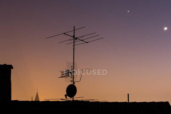 Silhouette der Antenne auf dem Dach des Gebäudes vor farbenfrohen Sonnenuntergang Himmel — Stockfoto
