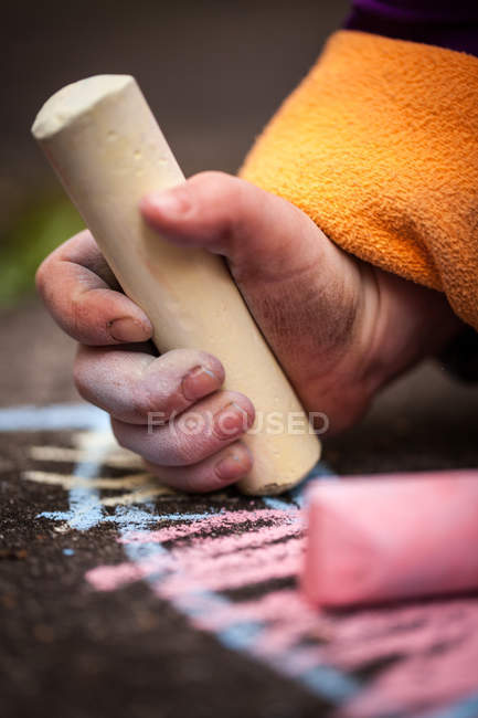 Close-up view of child hand holding colorful chalk — Stock Photo