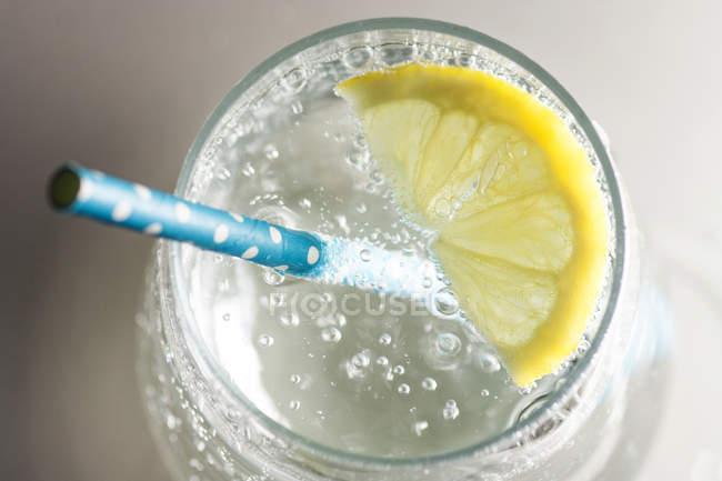 Draufsicht der Glas gefüllt mit Mineralwasser mit Zitronenscheibe und Trinkhalm — Stockfoto