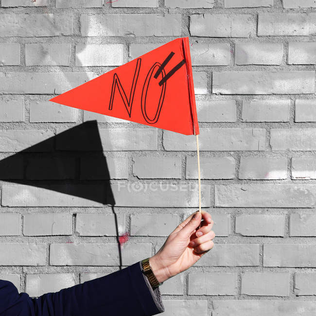 Person hand holding red triangle flag with no word — Stock Photo