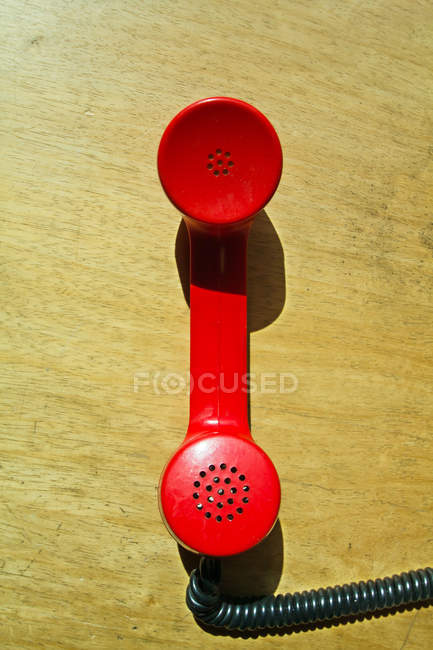 Red telephone handset with cable on wooden surface — Stock Photo