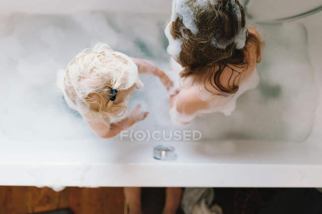 Vista dall'alto di due bambini fare il bagno nella vasca con schiuma — Foto stock
