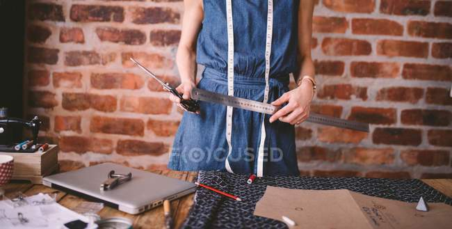 Cropped view of female dressmaker with ruler working with pattern — Stock Photo