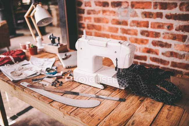 Tailor workshop with tools and machine on table — Stock Photo