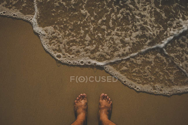b87cba47ff90 Looking down view of person feet on beach — wide angle