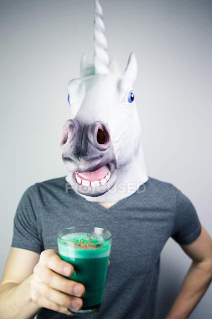 Человек, носящий Единорог головы маски и проведение зеленый напиток в стекле — стоковое фото