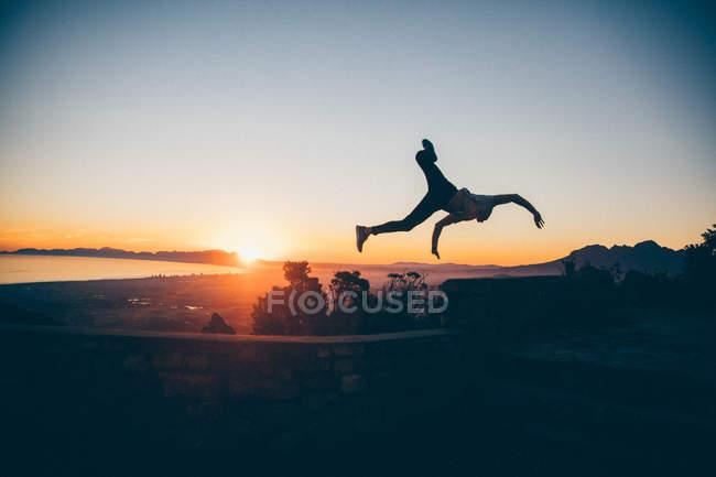 Homme sautant haut au coucher du soleil — Photo de stock
