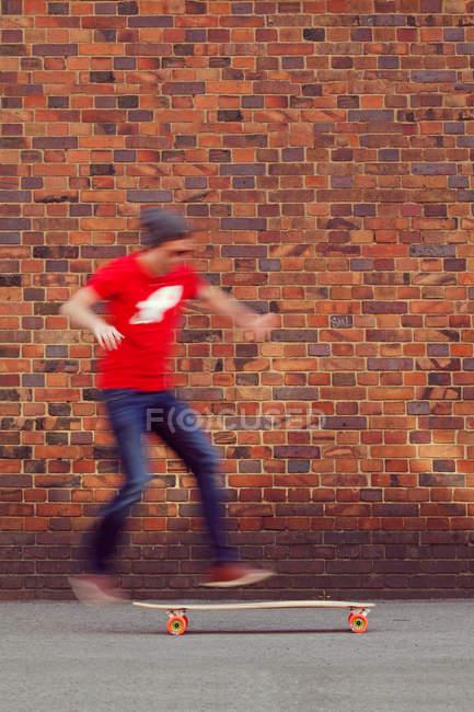 Junger Mann in Motion blur mit Longboard von Mauer — Stockfoto