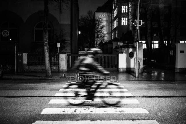 Bewegungsunschärfe Schuss der Radfahrer fahren Fahrrad in der Stadt bei Nacht — Stockfoto