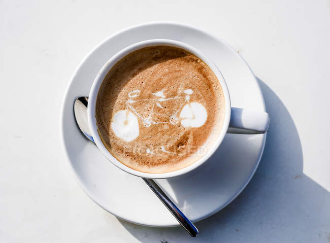 Top view of cup of cappuccino with bicycle art — Stock Photo