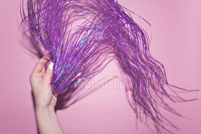 Teilansicht des weiblichen Hand mit lila Partei Lametta im studio — Stockfoto