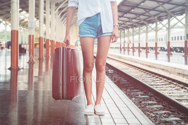 Cropped image de femme tenant voyage sac et debout sur la plate-forme de la voie ferrée — Photo de stock