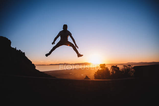 Young man jumping high in sunset — Stock Photo