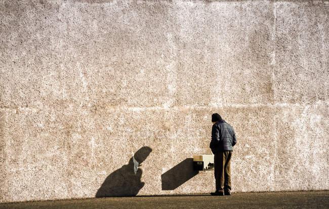 Vue arrière de l'homme debout à côté de la paroi du bâtiment gris — Photo de stock