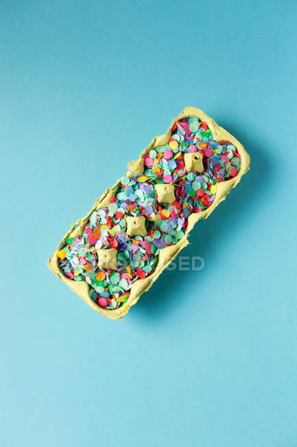 Cartón de huevos con confeti multicolor - foto de stock
