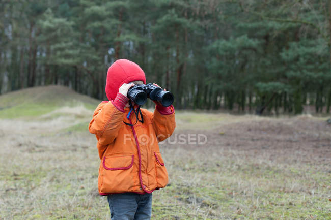 Garoto no casaco laranja, olhando através de binóculos, floresta no fundo — Fotografia de Stock