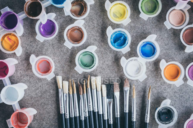Paint brushes and paint tubes isolated on table surface — Stock Photo