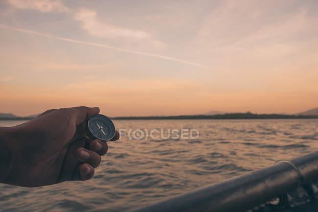 Mano con la bussola in spiaggia — Foto stock