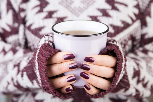 Woman in cozy sweater holding cup — Stock Photo