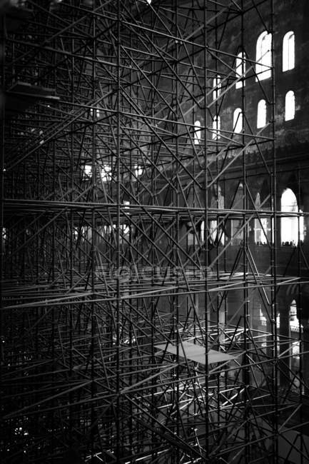 Scaffolding by the church walls with windows, interior view — Stock Photo